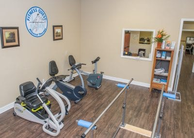 nustep and recumbent bikes in rehab area with parallel bar platform area
