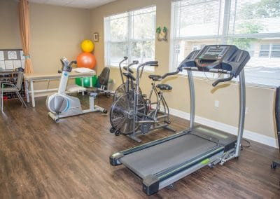 treadmill, stationary bikes and upper body ergometer in treatment area of physical therapy clinic
