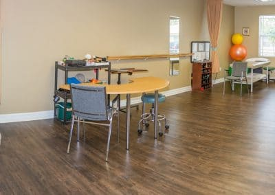 Treatment tables in open gym area cardio equipment and manual therapy desk