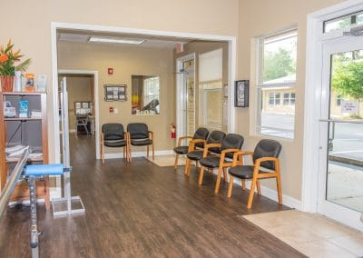 waiting room with multiple chairs inside physical therapy clinic