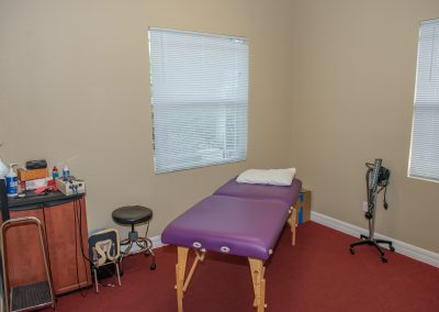 physical therapy private exam room with table and treatment supplies
