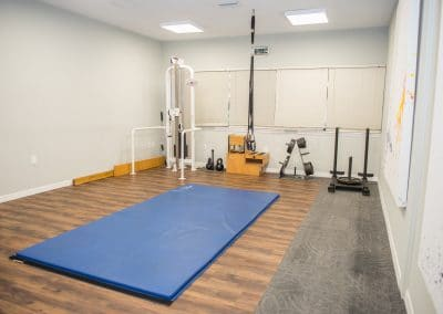 Physical Therapy open gym area with exercise floor mat, kettlebells and weights