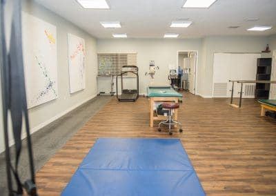Physical Therapy clinic in Bradenton gym area with treadmill, balance bars and treatment tables
