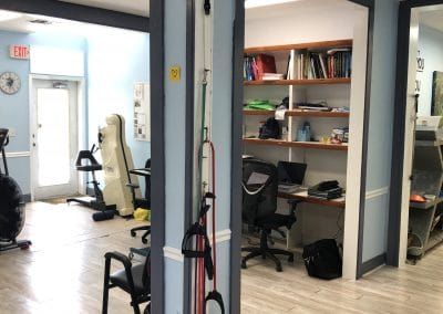 physical therapy open gym area with exercise bands, UBE and provider desk