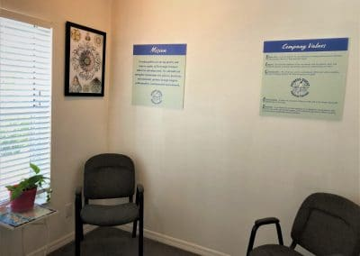 Physical Therapy waiting room area reception chairs and mission statement and values hanging on wall