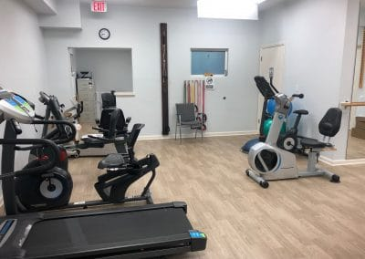 Physical Therapy clinic treatment area with treadmill and UBE and cardio equipment