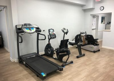 Physical Therapy clinic treatment area with treadmill and cardio equipment