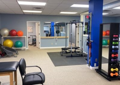 outpatient physical therapy clinic gym area with weights and treatment tables